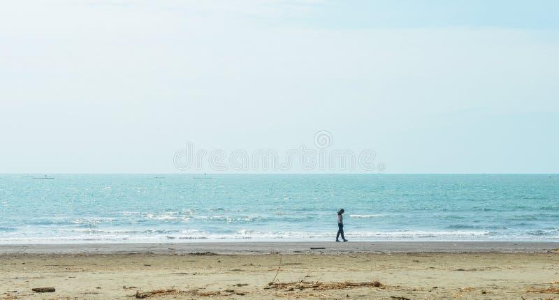 Fille asiatique simple marchant le long de la côte photographie stock