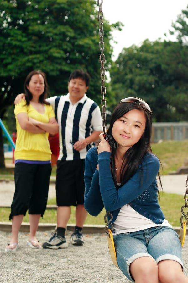 Fille asiatique sur l'oscillation avec des parents photos stock