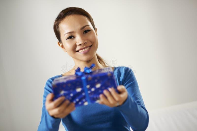 Fille asiatique tenant le boîte-cadeau sur l'appareil-photo images libres de droits