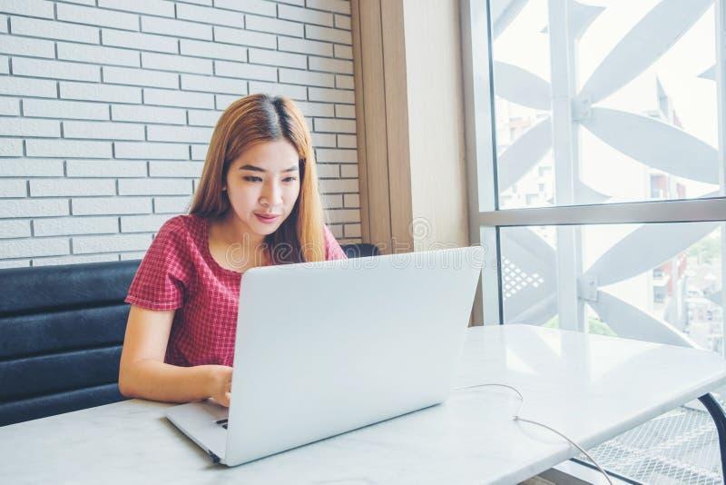 Fille asiatique travaillant à un café avec un ordinateur portable freelan femelle images libres de droits