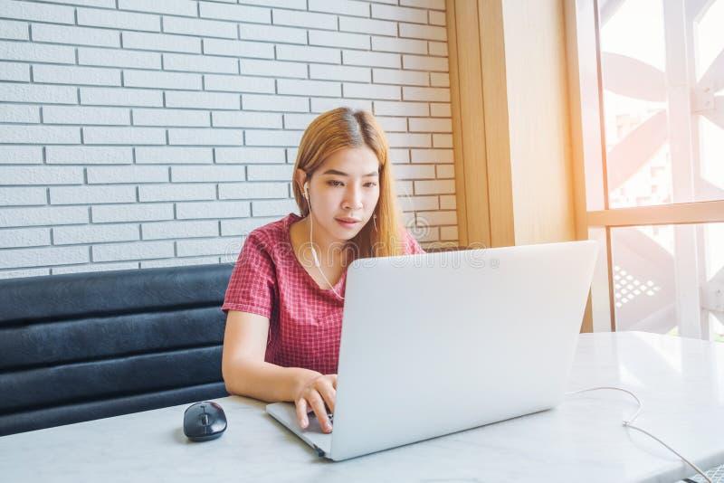 Fille asiatique travaillant à un café avec un ordinateur portable freelan femelle images stock
