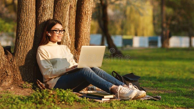 Fille asiatique utilisant l'ordinateur portable se reposant sous l'arbre au campus universitaire image stock
