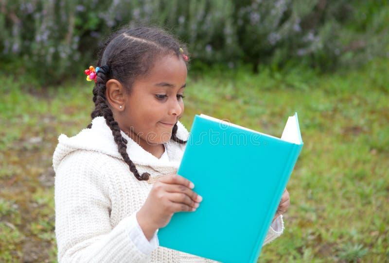 Fille assez africaine en parc lisant un livre images libres de droits