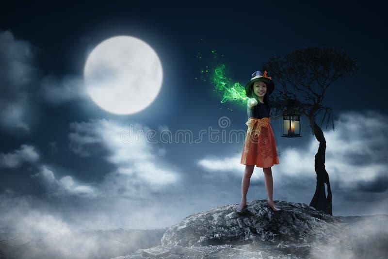 Fille assez asiatique d'enfant dans la baguette magique de magie d'utilisation de costume de sorcière photos libres de droits