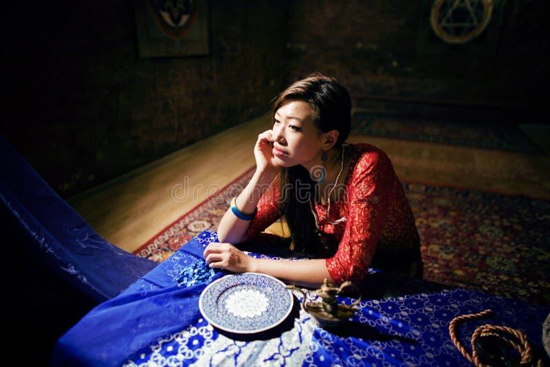 Fille assez asiatique de jeunes dans le salon féerique coloré lumineux intérieur sur le Vietnamien de tapis, concept différent de photographie stock libre de droits
