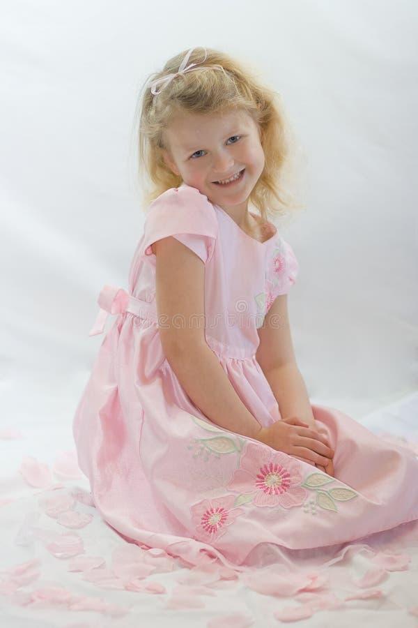 Fille assez blonde dans la séance rose dans des pétales roses. photographie stock libre de droits
