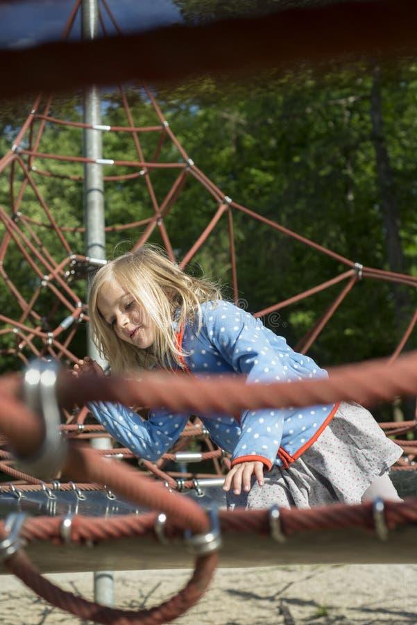 Fille assez blonde jouant sur la corde du Web rouge en été image stock
