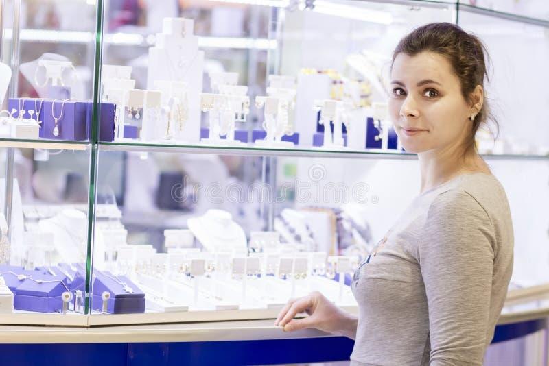 Fille assez jeune attirante près d'un étalage avec des bijoux Bijoux d'achat pour votre femme aimée images stock