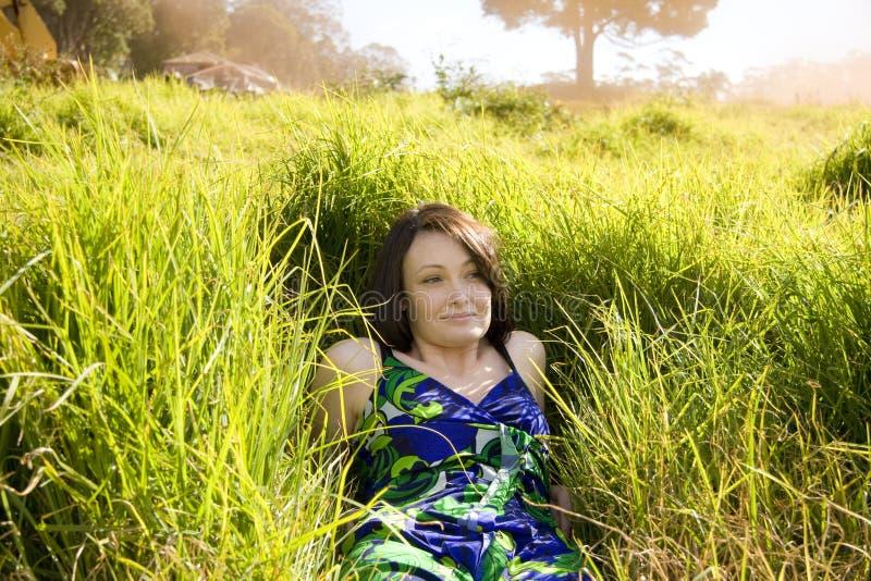 Fille assez jeune dans l'herbe photographie stock libre de droits