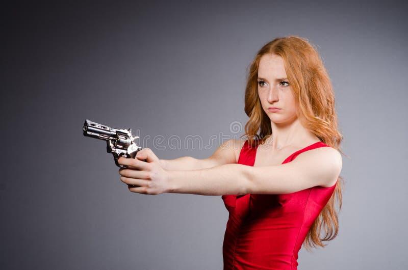 Fille assez jeune dans la robe rouge avec l'arme à feu images stock