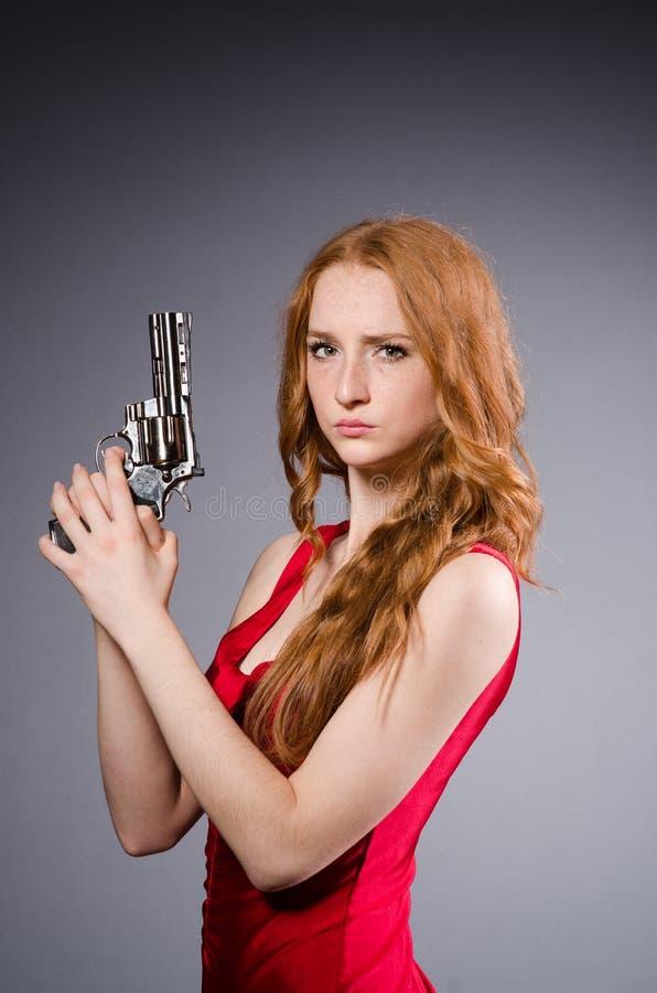 Fille assez jeune dans la robe rouge avec l'arme à feu d'isolement photos libres de droits