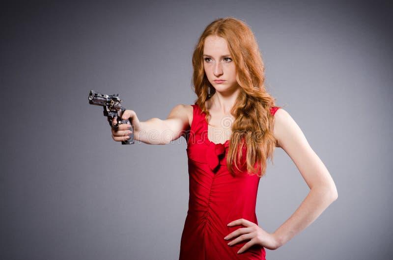 Fille assez jeune dans la robe rouge avec l'arme à feu d'isolement image stock