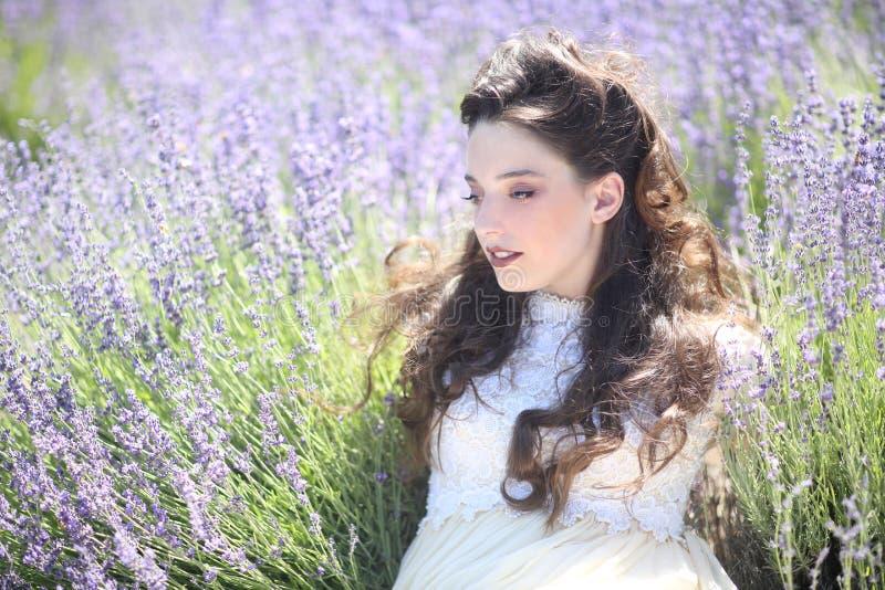 Fille assez jeune dehors dans un domaine de fleur de lavande image stock