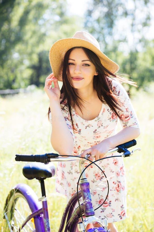 Fille assez jeune heureuse allant à vélo sur le parc d'été Heureux détendez le temps dans la ville Belle femme, jour ensoleillé photos stock