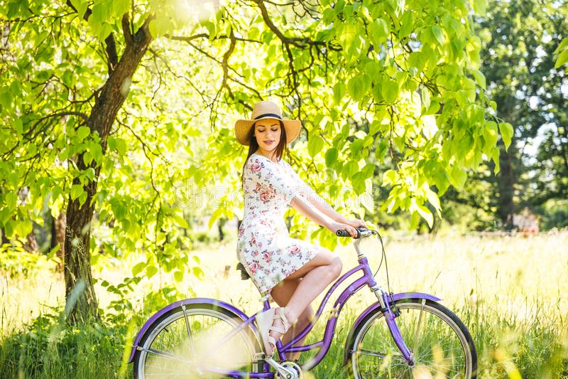 Fille assez jeune heureuse allant à vélo sur le parc d'été Heureux détendez le temps dans la ville Belle femme, jour ensoleillé image stock