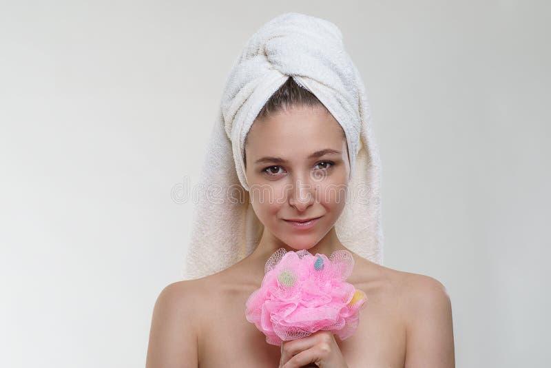 Fille assez jeune heureuse avec la belle peau fraîche et sourire merveilleux dans une serviette posant avec une éponge sur le fon images libres de droits