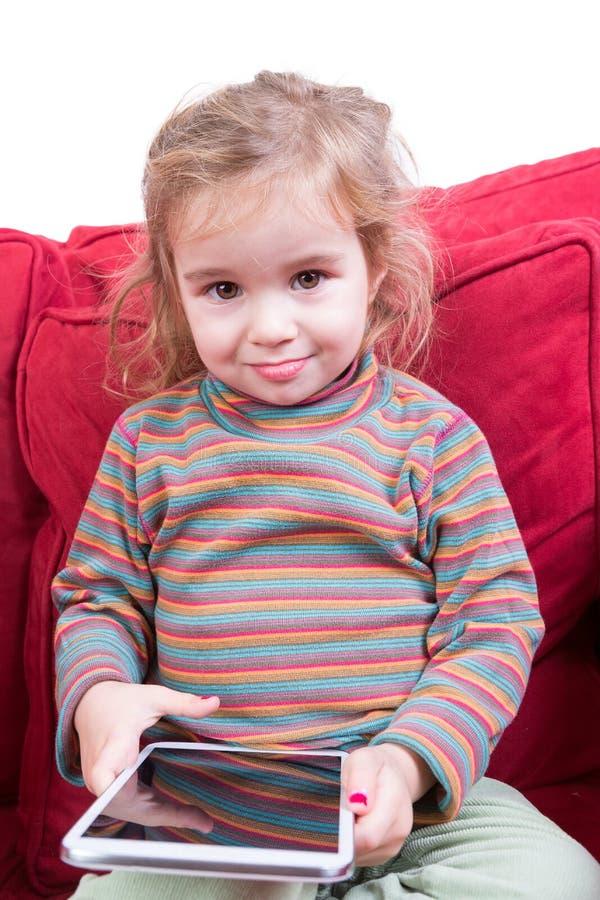 Fille assez jeune mignonne avec une tablette photographie stock