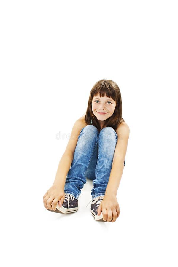 Fille assez jeune s'asseyant sur le plancher dans des jeans image libre de droits