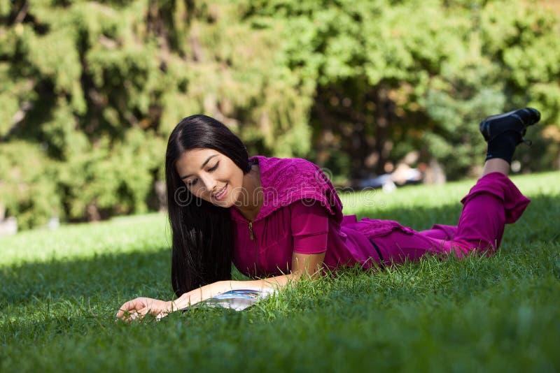 Fille assez jeune se trouvant sur l'herbe en parc, lisant le magazine image stock
