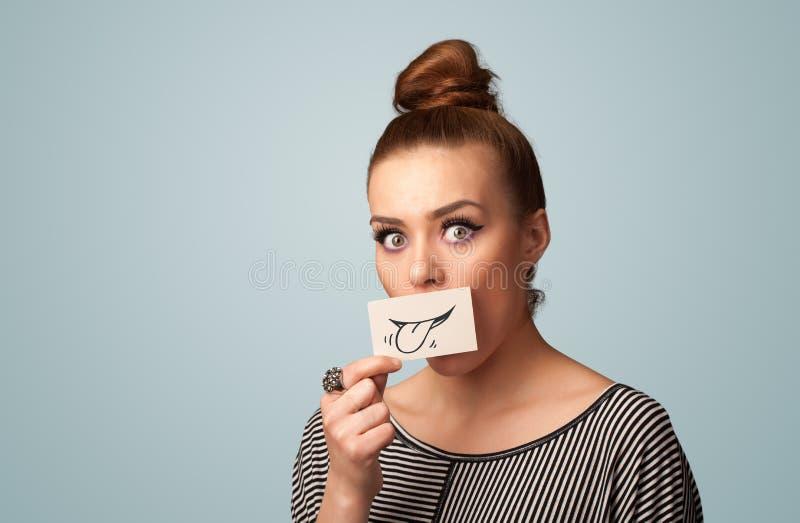Fille assez jeune tenant la carte blanche avec le dessin de sourire image libre de droits
