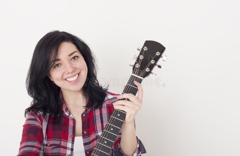 Fille assez jeune tenant un cou de guitare acoustique, regardant l'appareil-photo et le sourire photographie stock