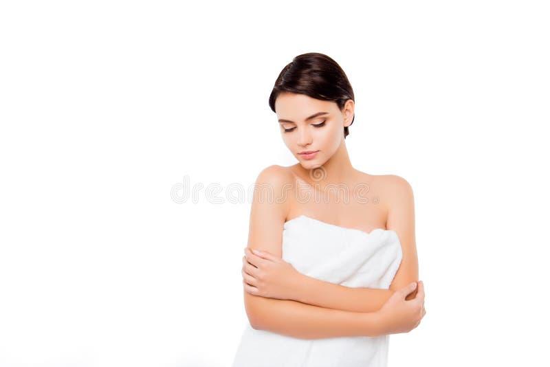 Fille assez mignonne de jeunes se tenant en serviette d'isolement sur le fond blanc, concept de thérapie de traitement de station photos libres de droits