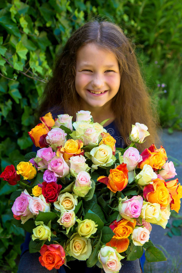 Fille assez petite avec le bouquet des roses de fleurs photo libre de droits