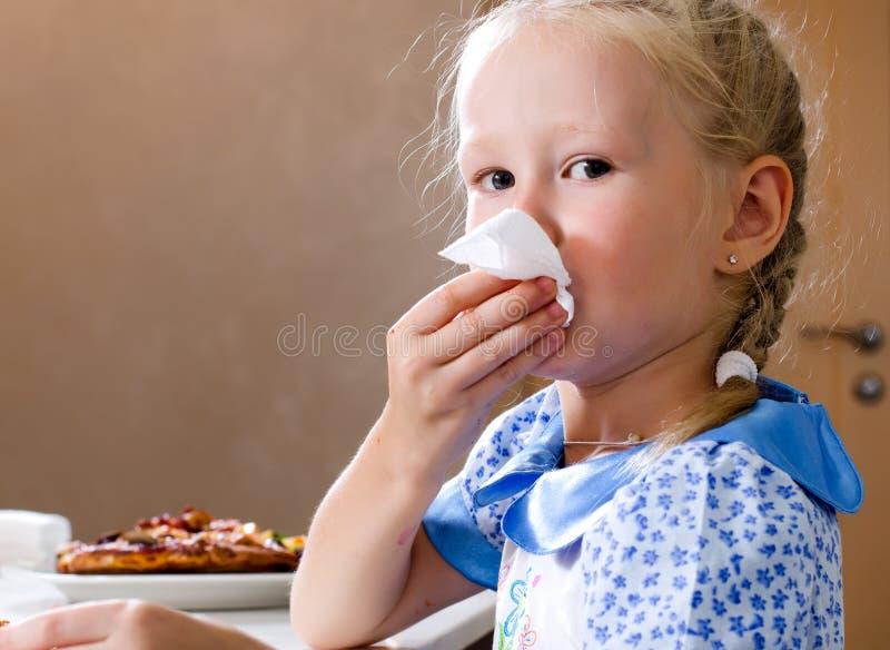 Fille assez petite essuyant sa bouche avec une serviette photographie stock libre de droits