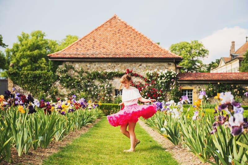 Fille assez petite jouant dans un beau jardin image libre de droits