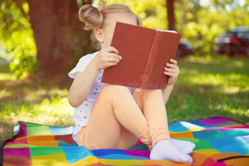 Download Fille Assez Petite Lisant Le Livre Rouge En Parc D'été Image stock - Image du fille, visage: 77151627