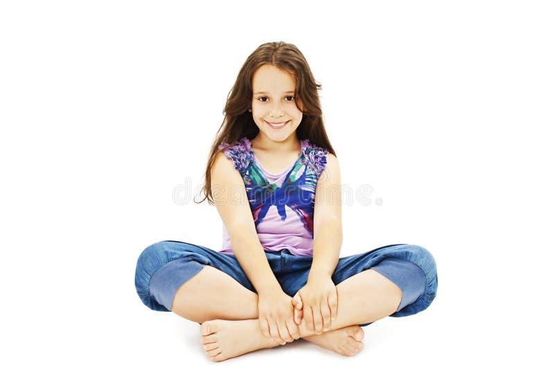 Fille assez petite s'asseyant sur le plancher dans des jeans photos stock