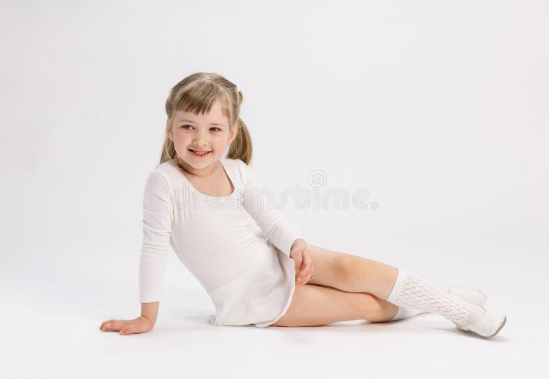 Fille assez petite s'asseyant sur le plancher et faisant l'exercice photos libres de droits