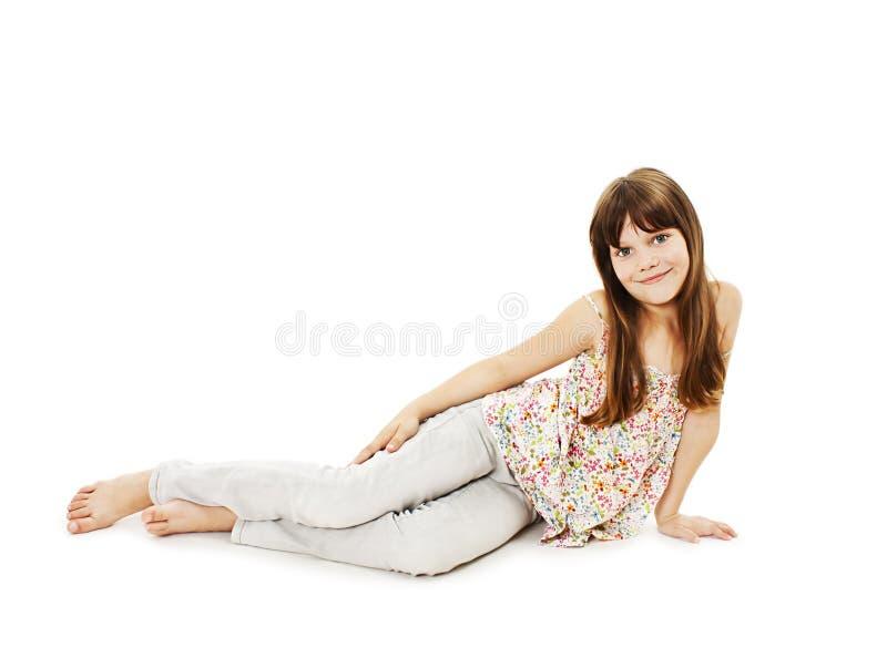 Fille assez petite se trouvant sur le plancher dans des jeans photos stock