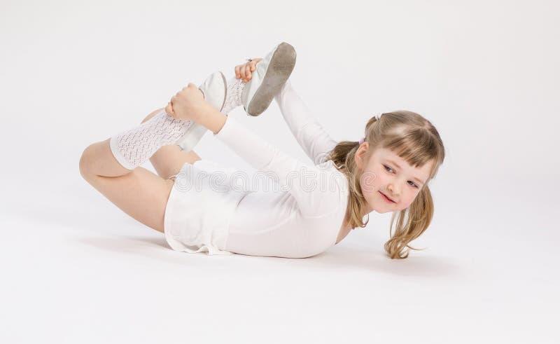 Fille assez petite se trouvant sur le plancher et faisant l'exercice image stock