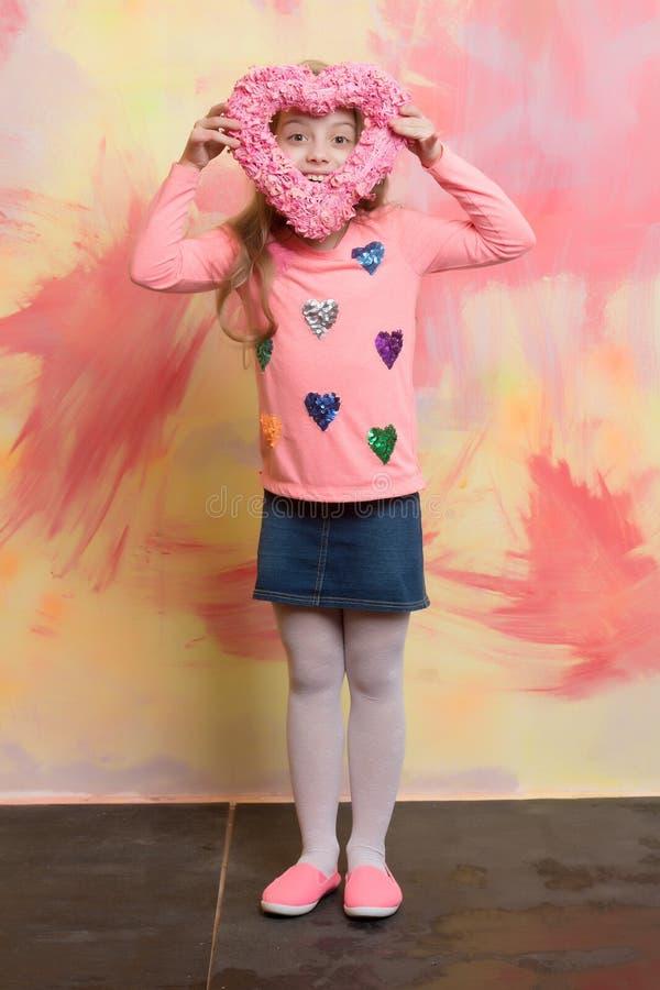 Fille assez petite sur l'enfant heureux de sourire avec le coeur rose image libre de droits