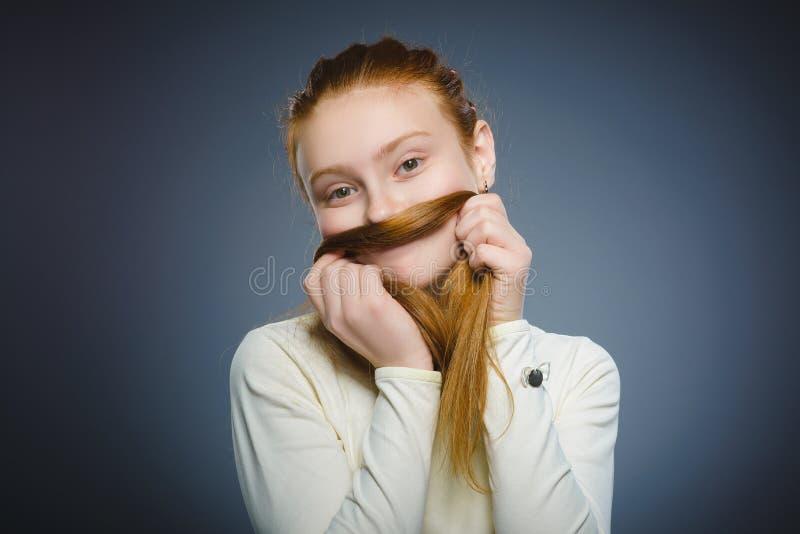 Fille assez rousse jouant avec ses cheveux d'isolement sur le gris images libres de droits