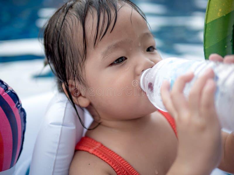 Fille assoiffée d'enfant se régénérant et la bouteille en plastique de forme d'eau potable dans la piscine photos stock