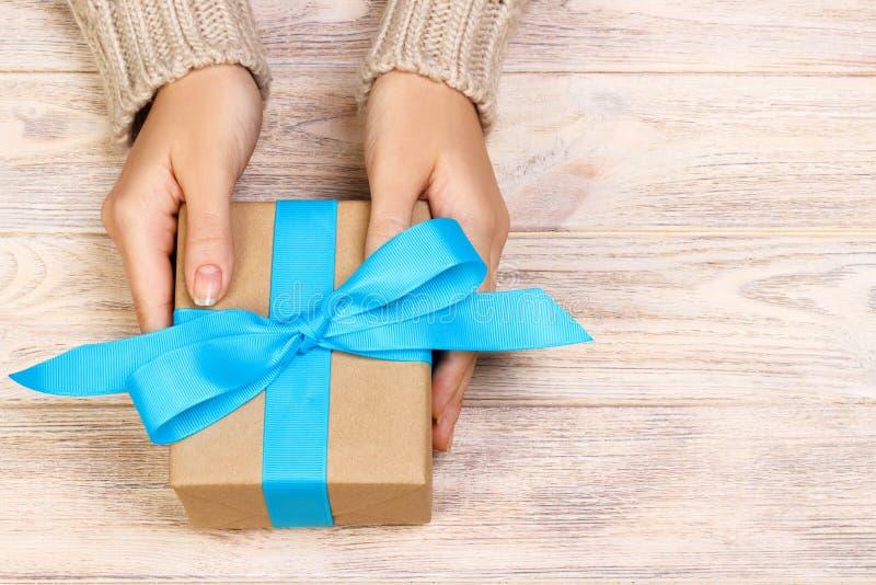 Fille attachant un arc bleu simple sur un boîte-cadeau Enveloppé dans le papier simple de métier et le ruban bleu Touche finale photos stock
