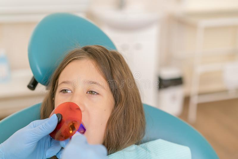 Fille atteignant le traitement remplissant dentaire la dent molaire avec la technologie ultra-violette Image de peu de fille ayan images stock