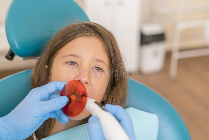 Fille atteignant le traitement remplissant dentaire la dent molaire avec la technologie ultra-violette Image de peu de fille fais image stock