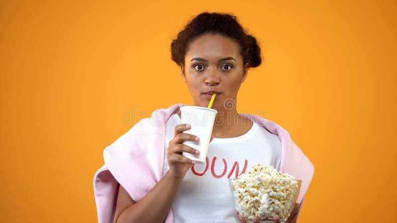 Fille attentivement observant le film et buvant la boisson non alcoolis?e, influence de t?l?vision image stock