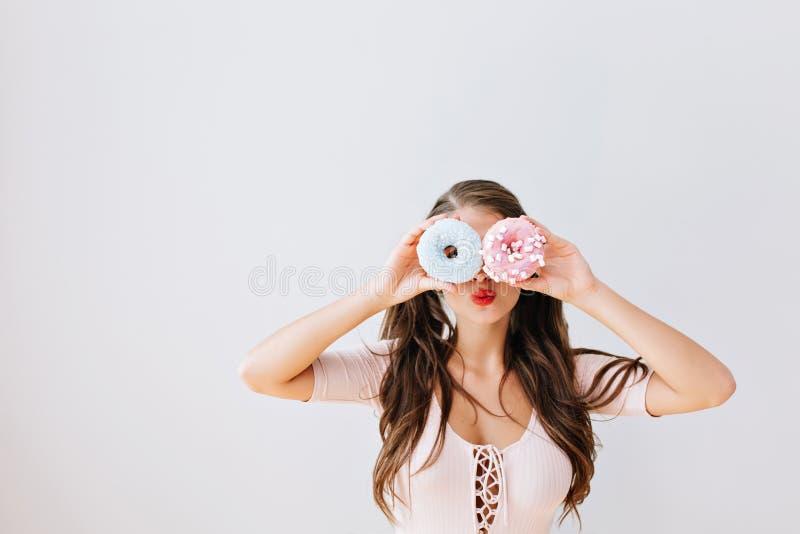 Fille attirante avec de longs cheveux de brune tenant les butées toriques colorées contre ses yeux Jeune femme joyeuse avec les l image stock