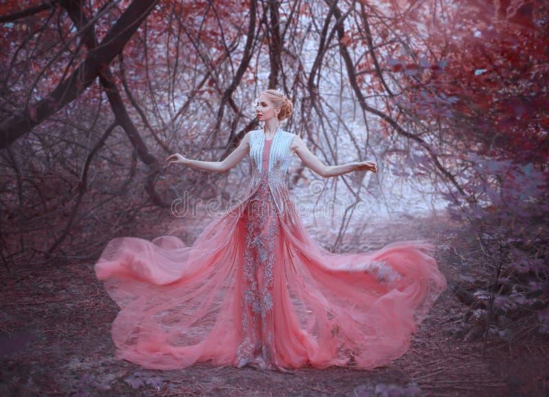 Fille attirante avec la coiffure blonde magnifique dans la forêt près des branches des arbres, habillées dans un rose étonnant lé photos stock