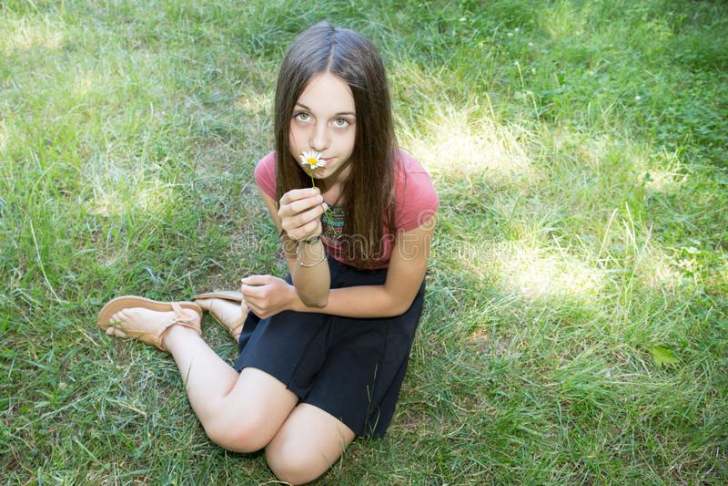 Fille attirante détendant sur l'herbe tenant des fleurs dans des ses mains photos stock