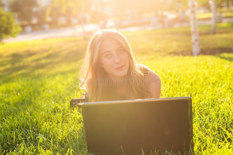 Fille attirante d'adolescent ayant l'amusement avec l'ordinateur portable dehors photos stock