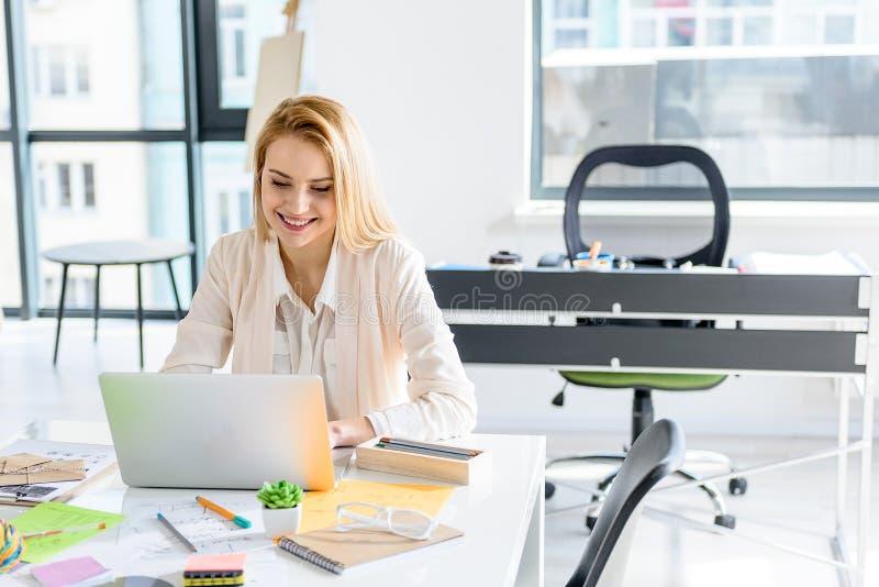 Fille attirante dactylographiant sur l'ordinateur avec le sourire photographie stock