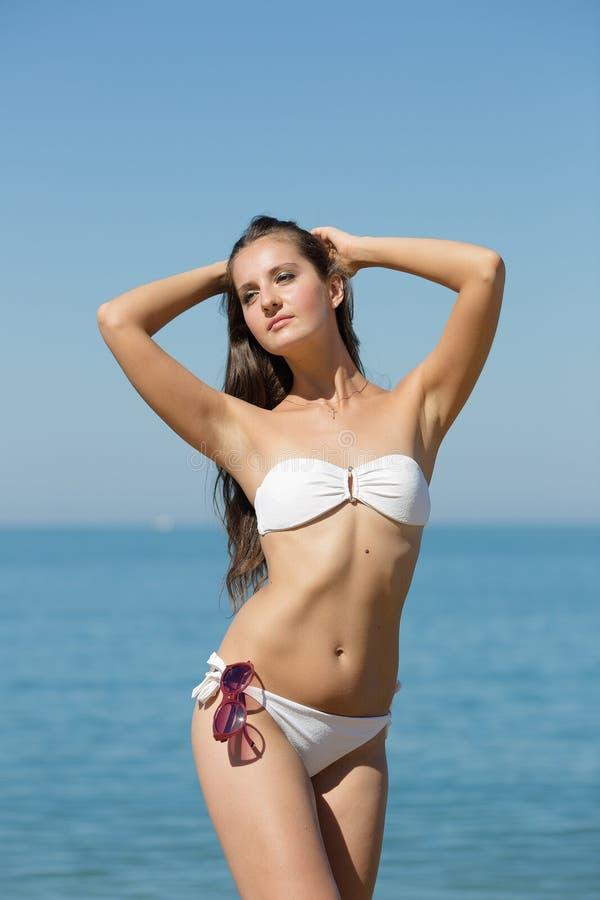Fille attirante dans le bikini blanc contre la mer photos libres de droits