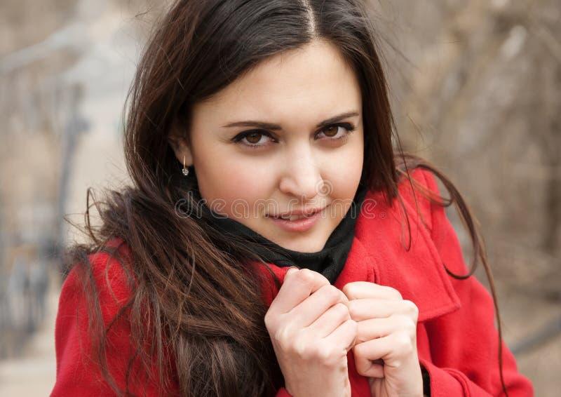Fille attirante dans le manteau rouge sur l'air de plein photo stock