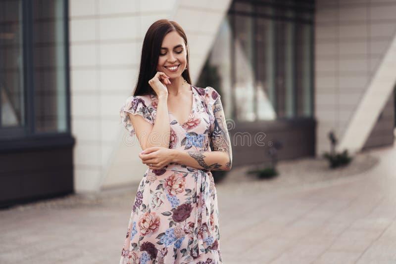 Fille attirante de brune dans la robe colorée posant près du centre d'affaires images libres de droits