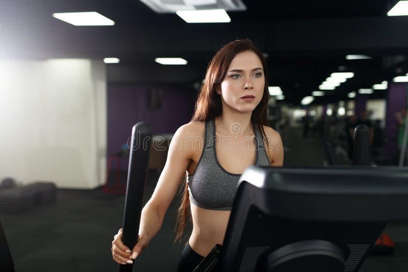 Fille attirante de forme physique faisant l'exercice sur le tapis roulant de machine Jolie fille faisant la séance d'entraînement image libre de droits